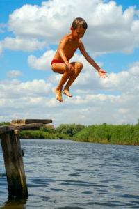 Little boy jumps into a river